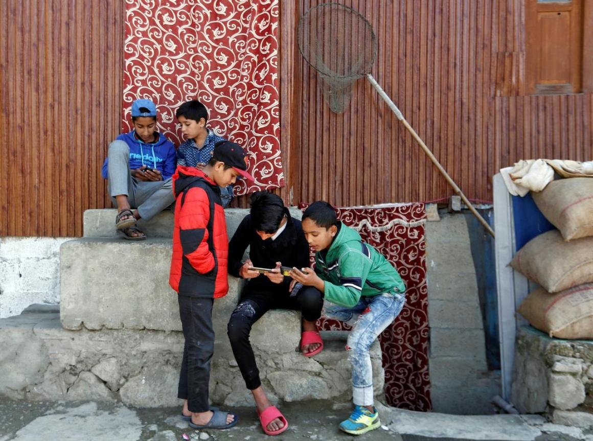 FILE PHOTO: Children play games on their mobile phones in a neighbourhood in Srinagar October 10, 2019. REUTERS/Danish Ismail