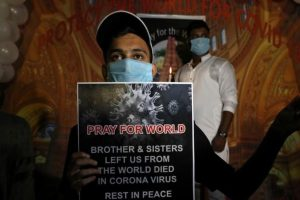 A man wearing a protective face mask holds a placard and a candle during a vigil for the people from around the world, who died due to the coronavirus disease (COVID-19), in Kolkata, India, September 23, 2020. REUTERS/Rupak De Chowdhuri