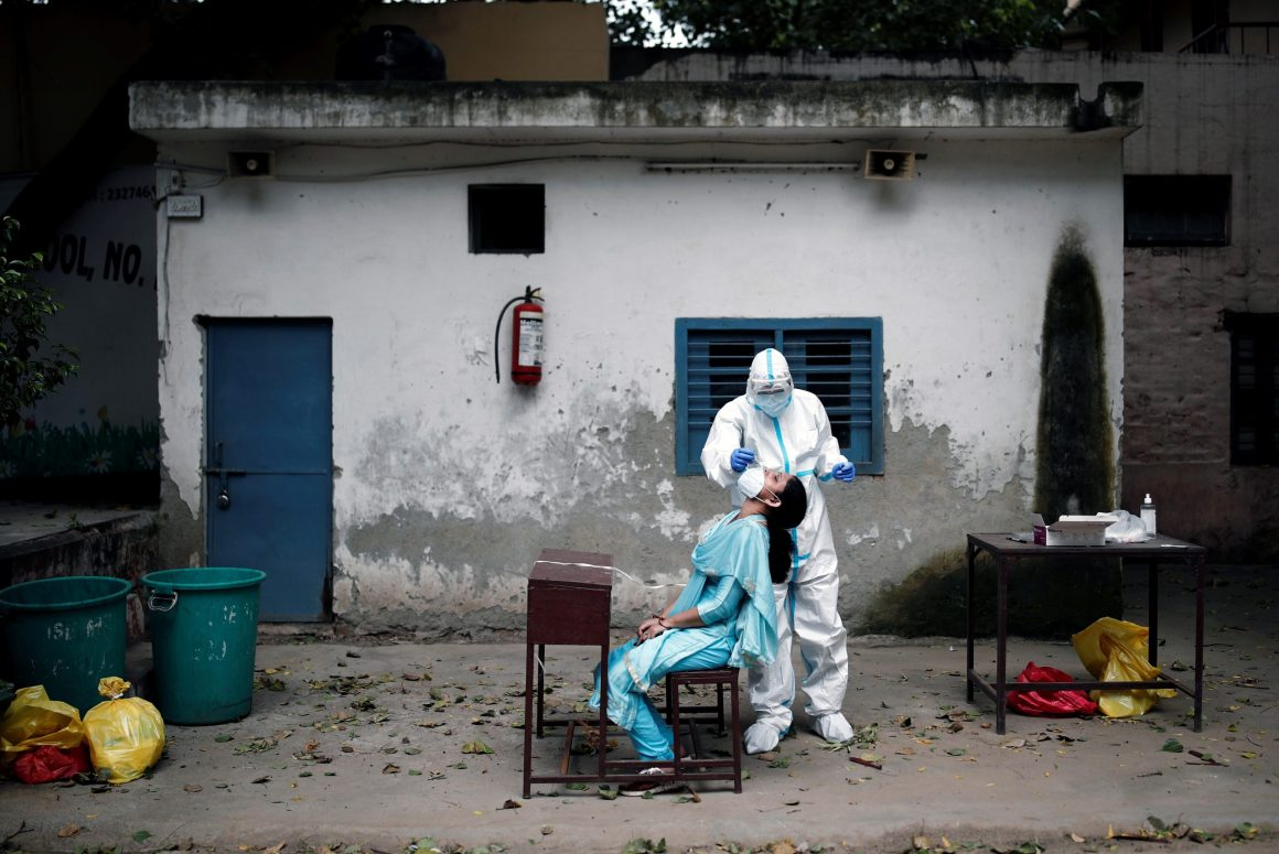 A health worker in personal protective equipment (PPE) collects a sample using a swab from a person at a school which was turned into a centre to conduct tests for the coronavirus disease (COVID-19), amidst the spread of the disease, in New Delhi, India, August 6, 2020. REUTERS/Adnan Abidi