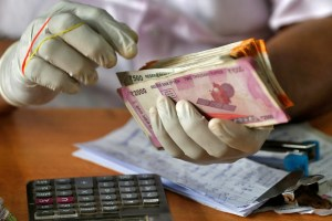 A trader wearing protective hand gloves counts Indian currency notes at a market during a 21-day nationwide lockdown to limit the spreading of coronavirus disease (COVID-19), in Kochi, India, March 27, 2020. REUTERS/Sivaram V