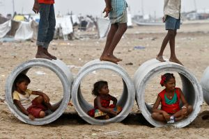 Children sitting inside cement water pipes play on the Marina beach in the southern Indian city of Chennai October 10, 2013. REUTERS/Babu