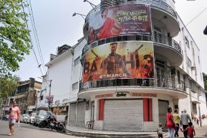 People walk past a cinema hall which is closed temporarily in the wake of deadly coronavirus, in Kolkata. PTI Photo