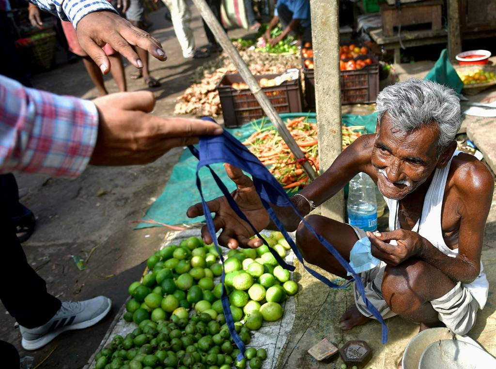 Agartala: Officials present a mask to a vegetable vendor during mask enforcement day as part of an initiative by the State Government to curb COVID-19 spread, in Agartala, Saturday, Oct. 10, 2020. (PTI Photo)(PTI10-10-2020 000080B)