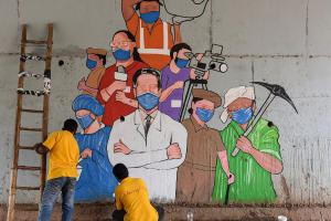 Artists paint a mural on COVID-19 frontline workers in Hubballi. Credit: PTI