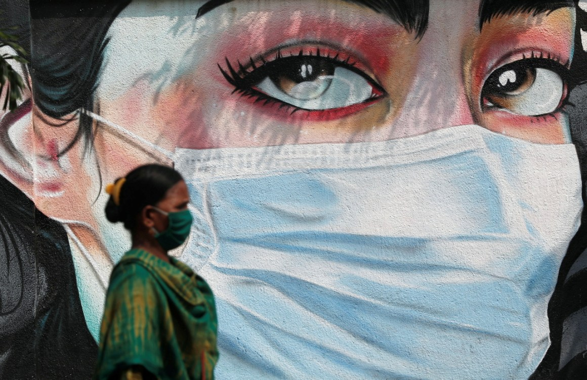A woman walks past a graffiti of a girl wearing a protective mask amidst the spread of the coronavirus disease (COVID-19) in Mumbai, India, October 23, 2020. REUTERS/Francis Mascarenhas