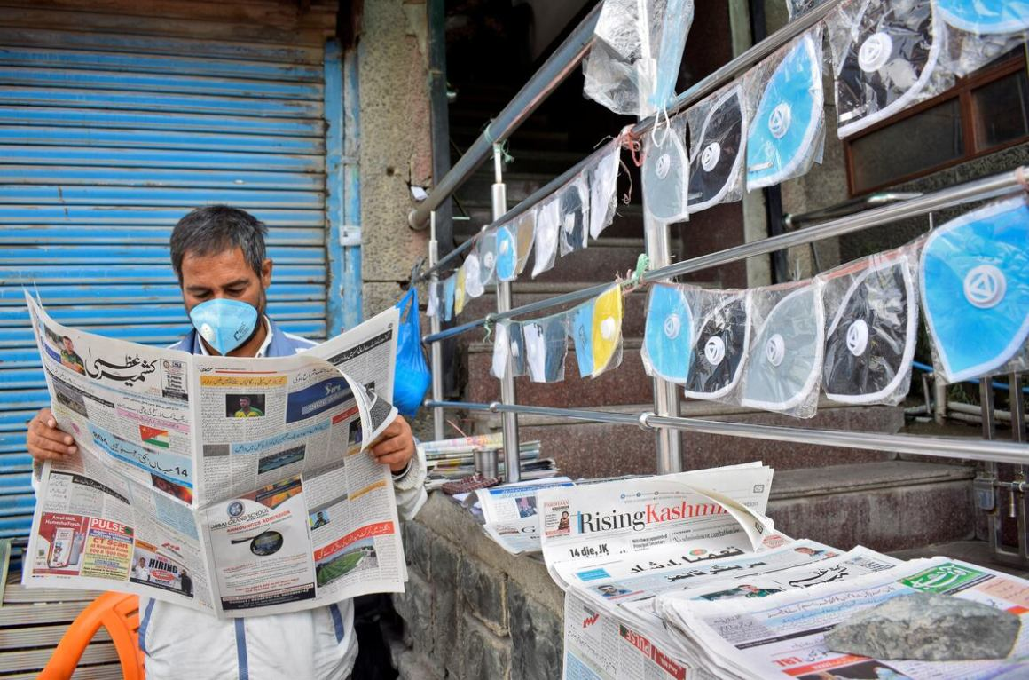 A vendor wearing a protective face mask reads a newspaper at his stall as he sells face masks and newspapers amidst the coronavirus disease (COVID-19) outbreak in Srinagar, September 7, 2020. REUTERS/Sanna Irshad Mattoo