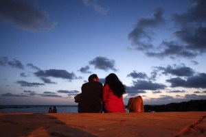 A couple sits along the seafront promenade at dusk in Mumbai's suburbs May 16, 2012. REUTERS/Vivek Prakash