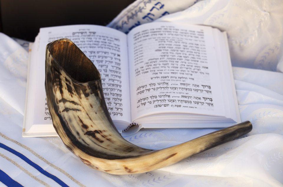 Shofar and Hebrew prayer book on a Talit (prayer Shawl).
