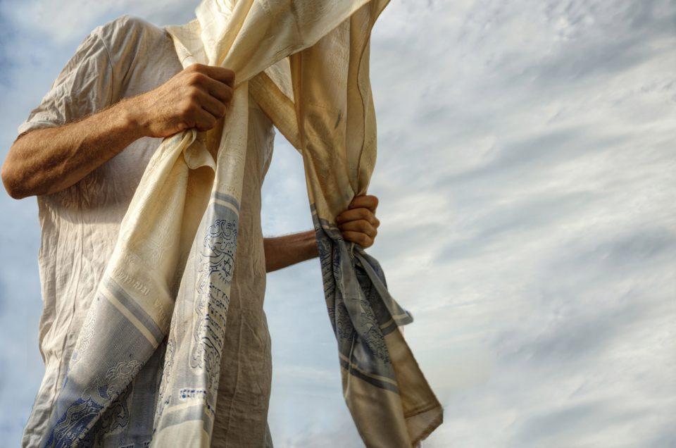 Jewish man engaged in morning prayers. He wears the traditional tallis (prayer shawl)
