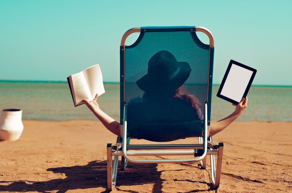 rear view of woman on lounge chair on the beach holding book and digital tablet.summer relaxing day.