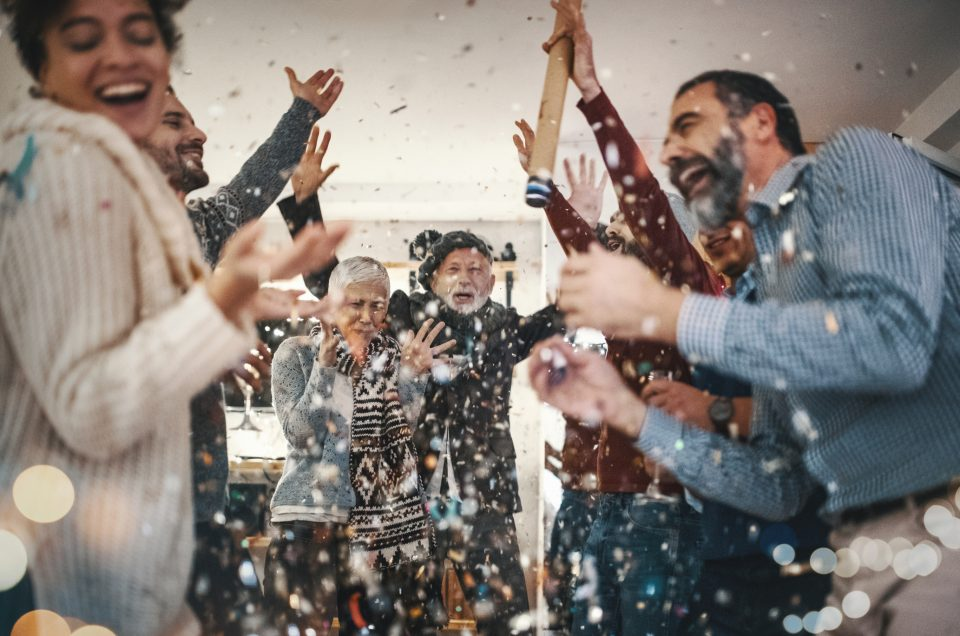 Closeup of group of mixed age people having New year's party at home. They are having champagne, lighting up some fire sparklers and popping confetti. There are two women and five men enjoying this party.