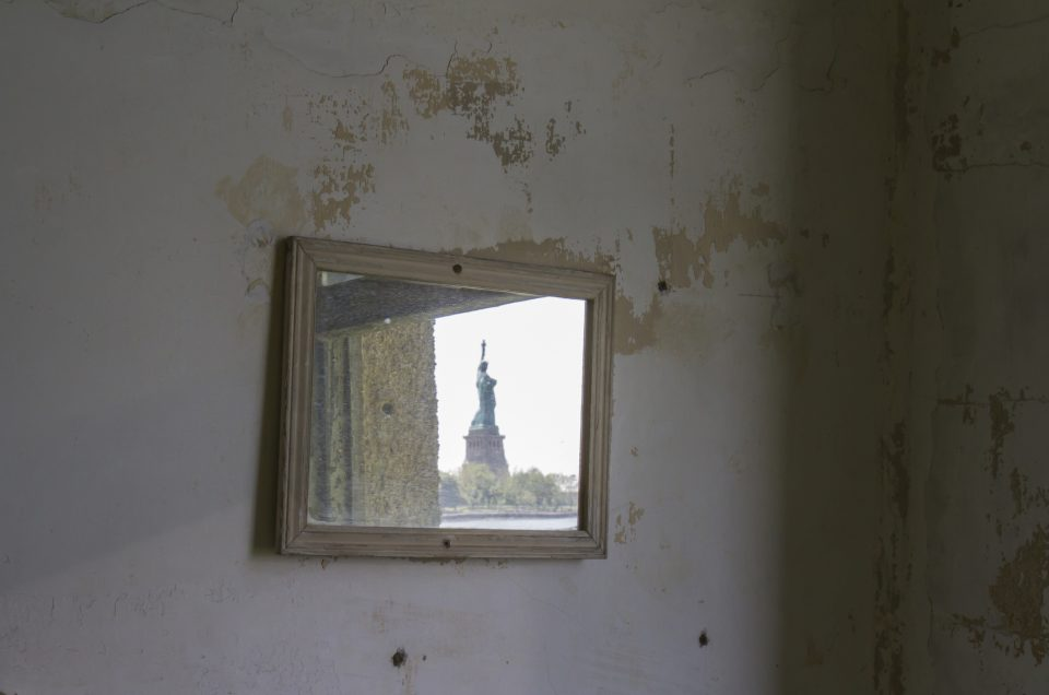 Statue of Liberty reflected in mirror above sink on wall of tuberculosis wing of Ellis Island hospital.