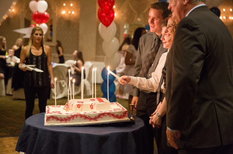 Bar Mitzvah boy lights candles on his cake with his family