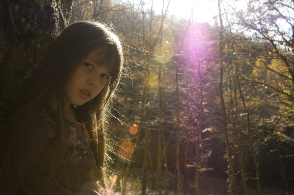 """A little girl outdoors posing. Lens flare, shade..."""