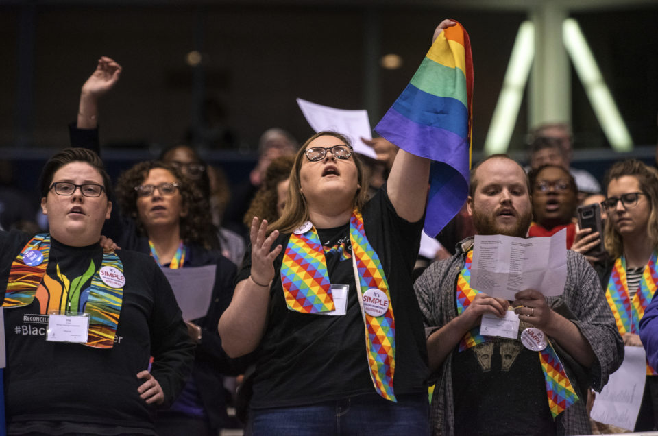 Shelby Ruch-Teegarden, center, of Garrett-Evangelical Theological Seminary joins other protestors during the United Methodist Church's special session of the general conference in St. Louis, Tuesday, Feb. 26, 2019. America's second-largest Protestant denomination faces a likely fracture as delegates at the crucial meeting move to strengthen bans on same-sex marriage and ordination of LGBT clergy. (AP Photo/Sid Hastings)