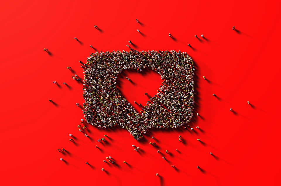 Human crowd forming a big heart shape on red background. Horizontal composition with copy space. Like and donation concept.