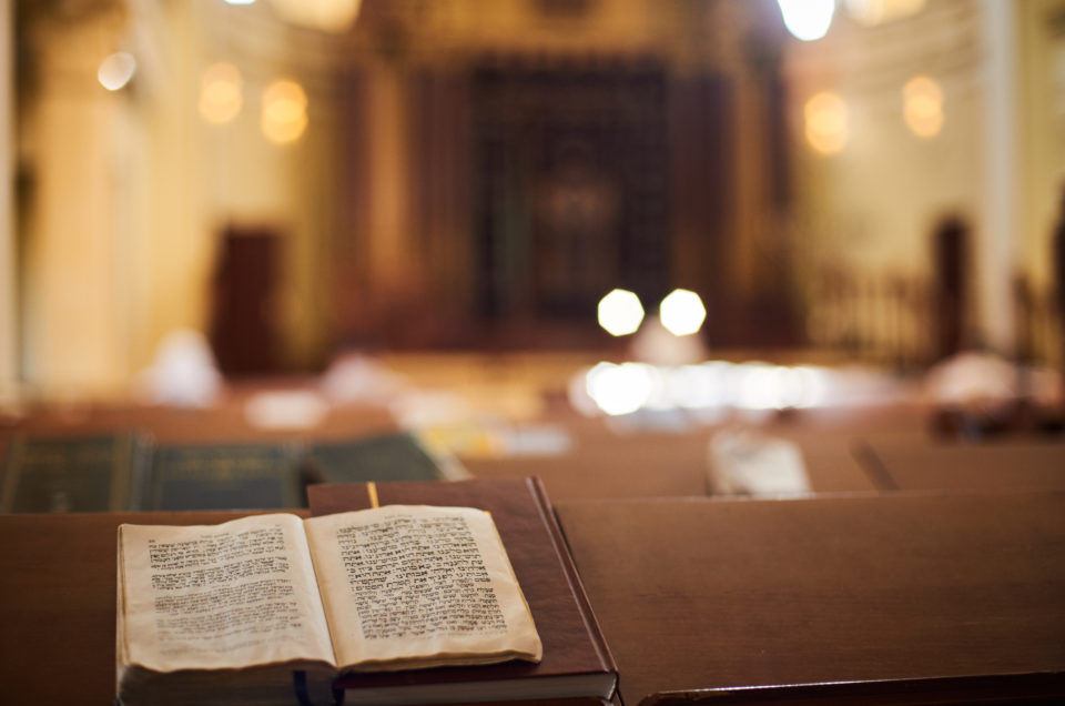 Inside of Orthodox Synagogue with open book in the Hebrew language in the foreground. selective focus.