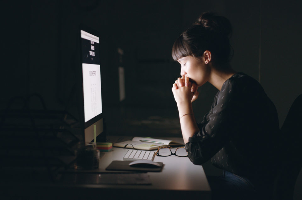 Shot of a young businesswoman sitting with her hands clasped while working on a computer in an office at night