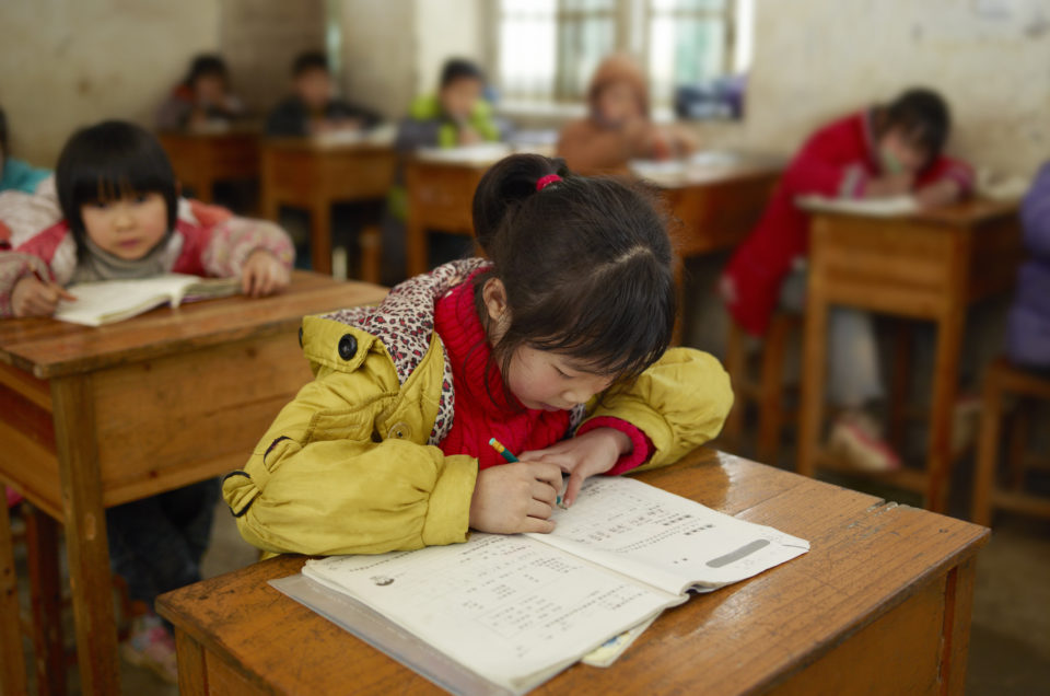 Chinese school girl writing in the classroom