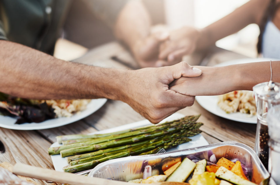 Cropped shot of a family holding hands in prayer before having a meal together
