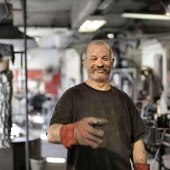 happy elderly worker smiling in workshop