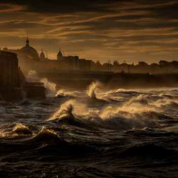 stormy sea waving on embankment of old city
