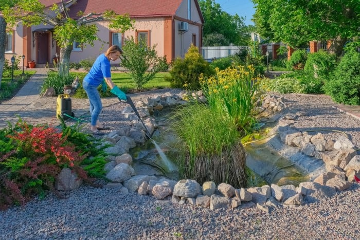 woman cleaning a backyard pond with a pressure washer