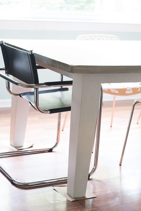 picture of black cantilever and white plastic chair at the table to show height