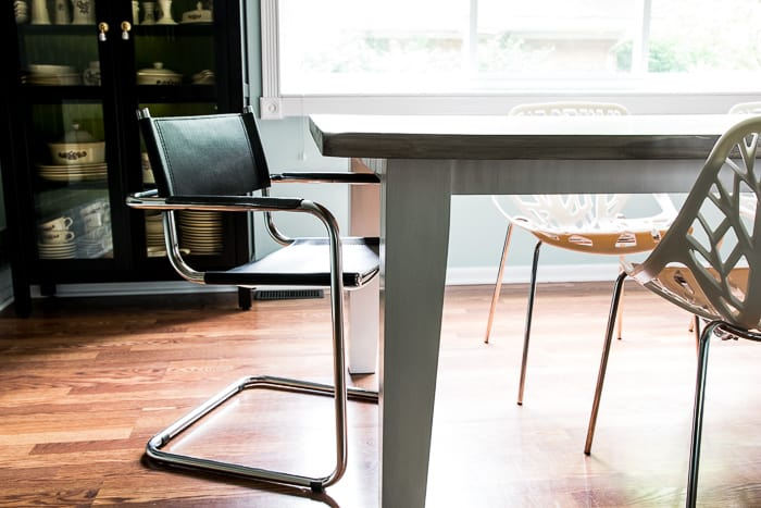 picture of black leather dining chair pulled out from table