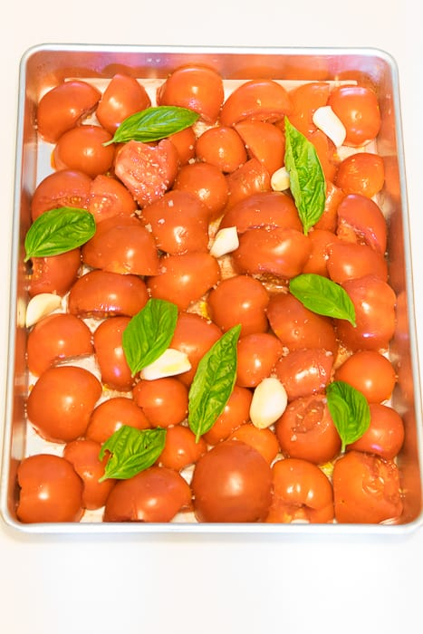 Picture of tomatoes, garlic and basil laves arranged in a single layer on a sheet pan