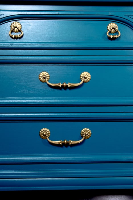 picture of teal drawers with gold hardware