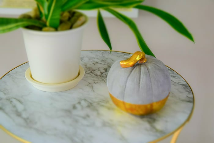 picture of round marble and gold table top with plant and concrete gold dipped pumpkin