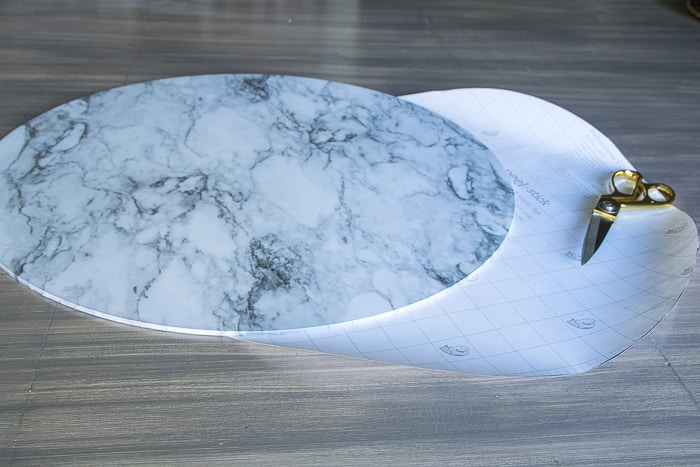 picture of marble covered glass round with second round piece of shelf paper cut out and golden scissors