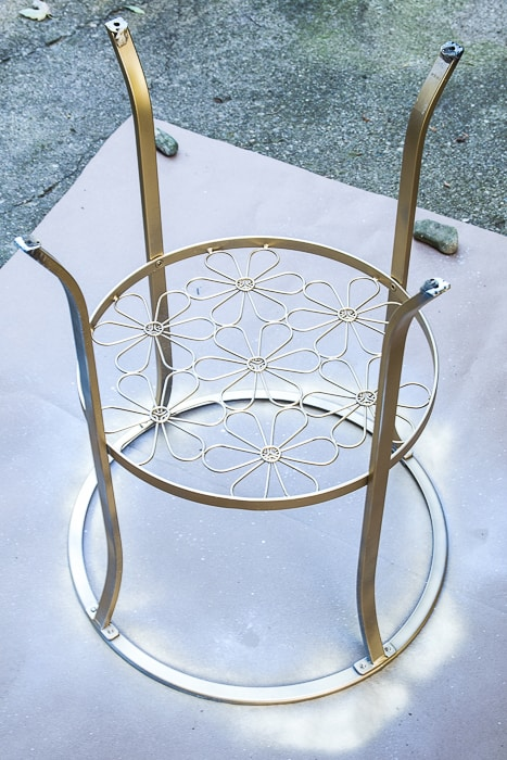 picture of primed and gold spray painted round metal table upside down outside