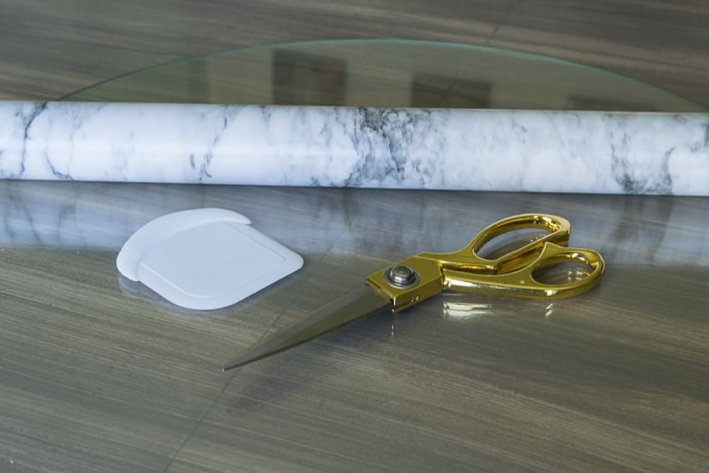 picture of marble shelf liner paper, gold scissors and plastic dough scraper