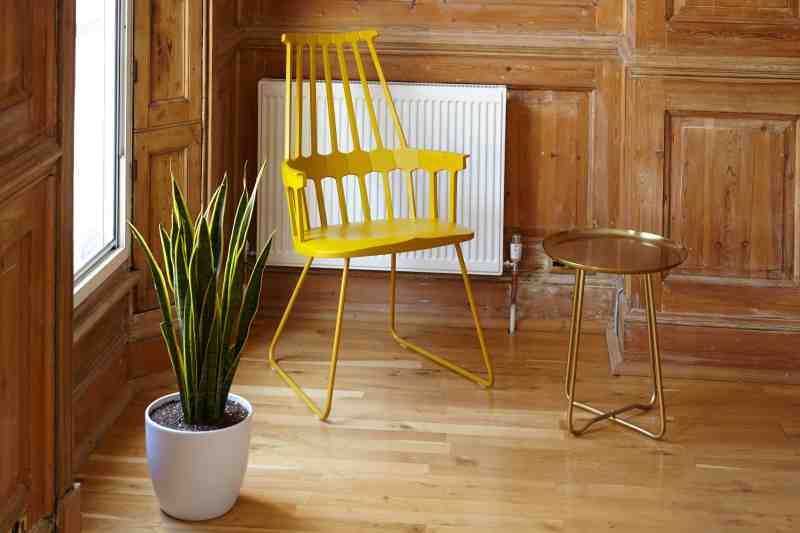 corner of a wood paneled room featuring a whimsical yellow chair, metal side table and white planter with a snake plant