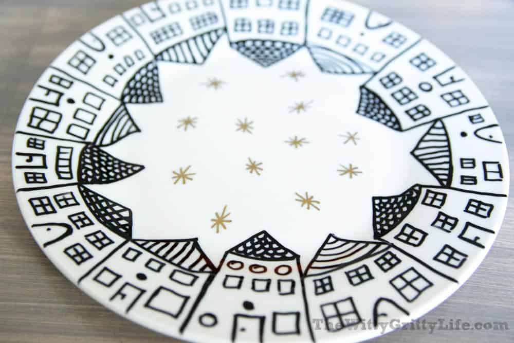 white plate with black houses around the rim and gold stars in the center