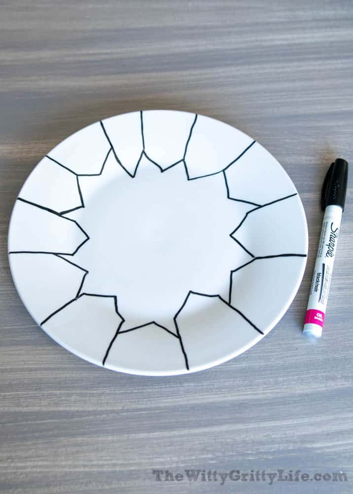 white plate with black outline of houses drawn on