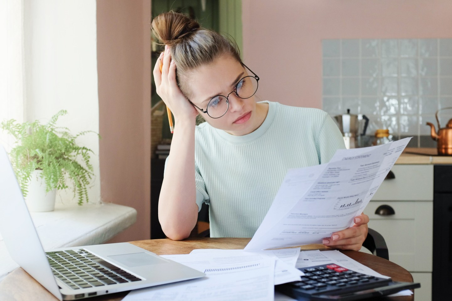 Young frustrated unhappy tired woman with financial troubles, sitting at kitchen table with papers, calculator and laptop computer, reading documents