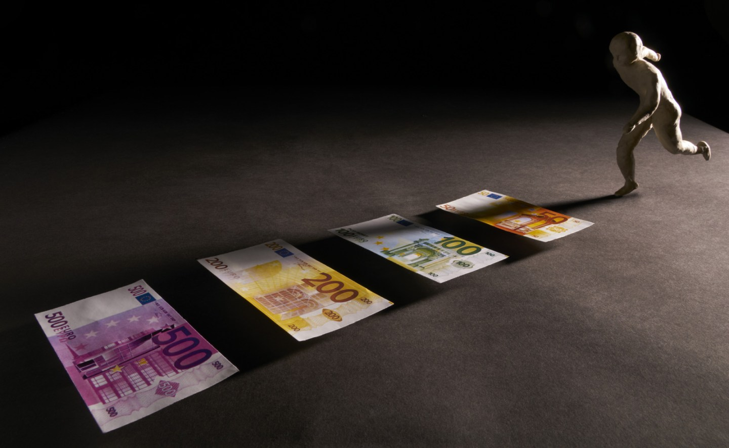 Man run on a track in money. Metaphor sport and money. Isolated on dark background. With copy space text. Studio Shoot.