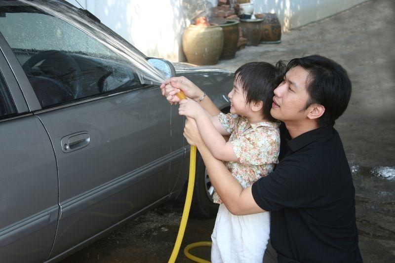 man and kid washing car