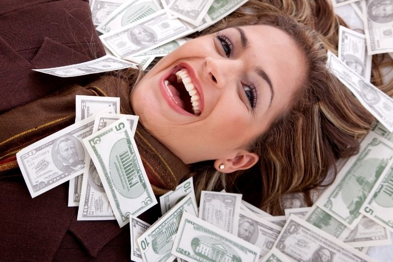 millionaire business woman with money around her face