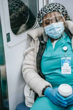 exhausted black nurse in mask sleeping in metro train