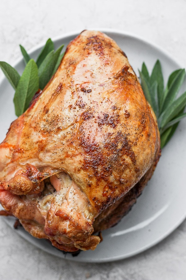 Top down shot of a cooked turkey breast sitting on a plate with sprigs of fresh sage on either side.
