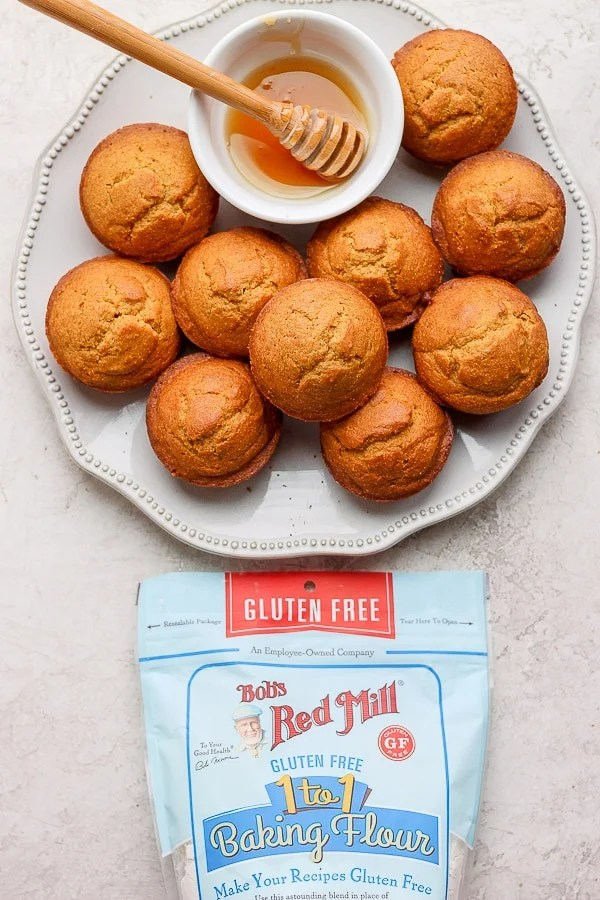 A pile of cornbread muffins on a white plate with a small bowl of honey next to a bag of Bob's Red Mill 1 to 1 baking flour.
