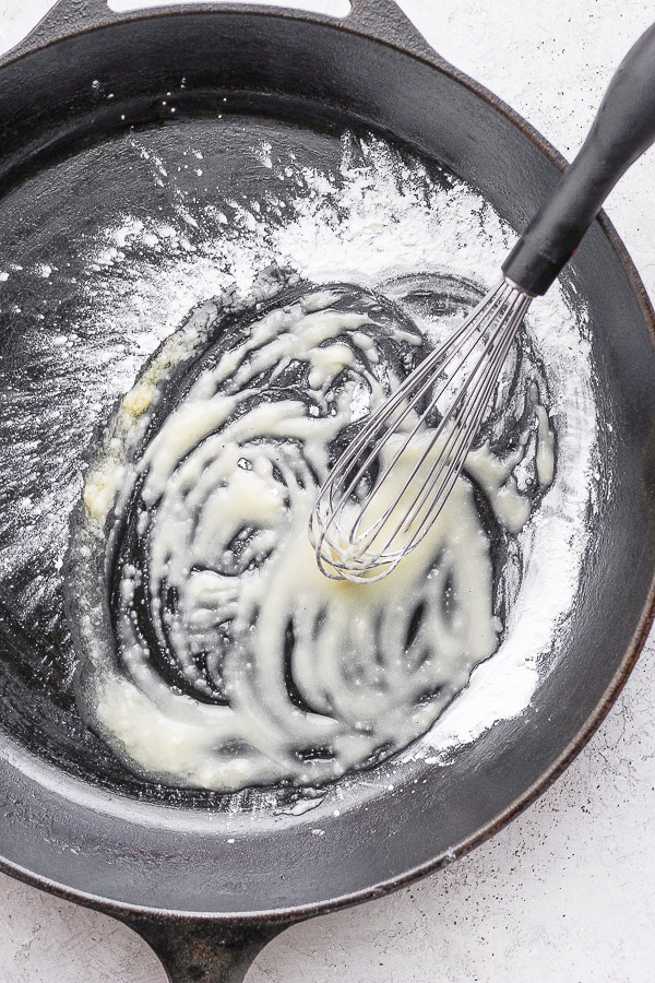 Cast iron skillet with a whisk combining melted ghee and tapioca starch.