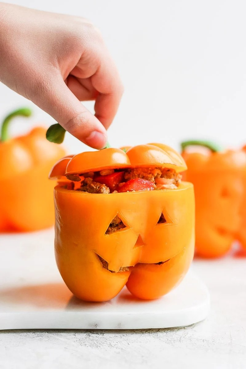 A jack-o-lantern stuffed pepper with a hand lifting the top slightly so you can see the stuffing inside.