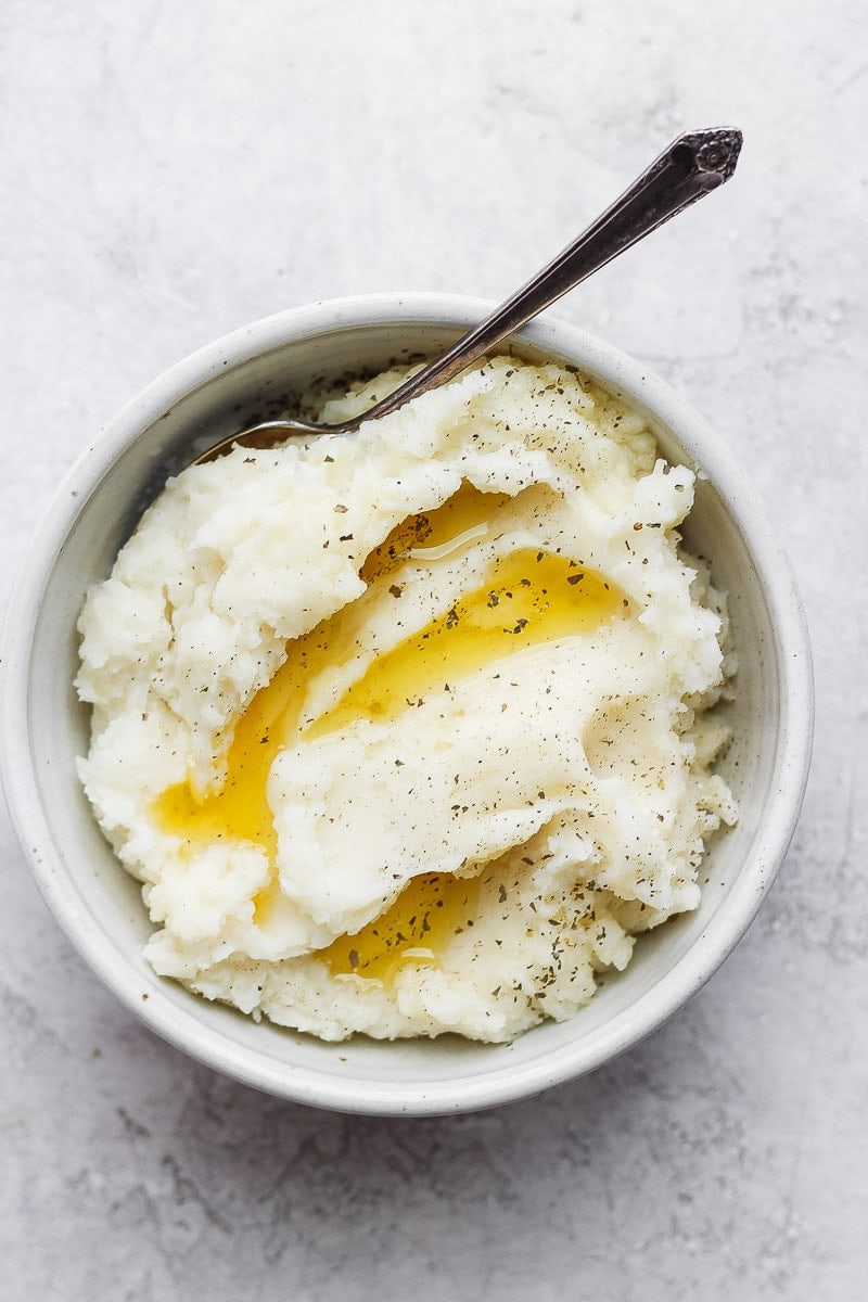 Bowl of mashed potatoes with melted ghee, salt, and pepper on top and a spoon.