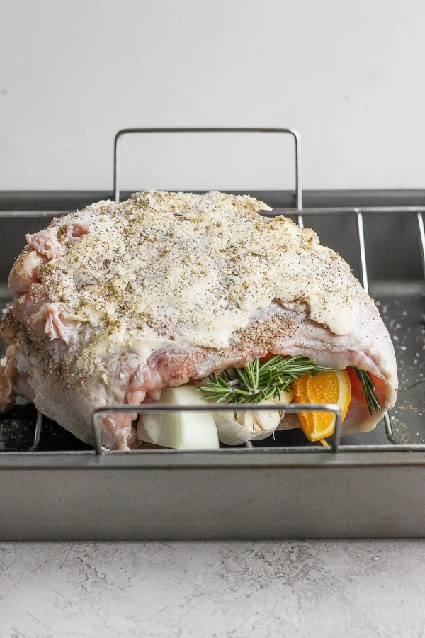 A prepared and stuffing turkey breast sitting in a roasting pan, uncooked.