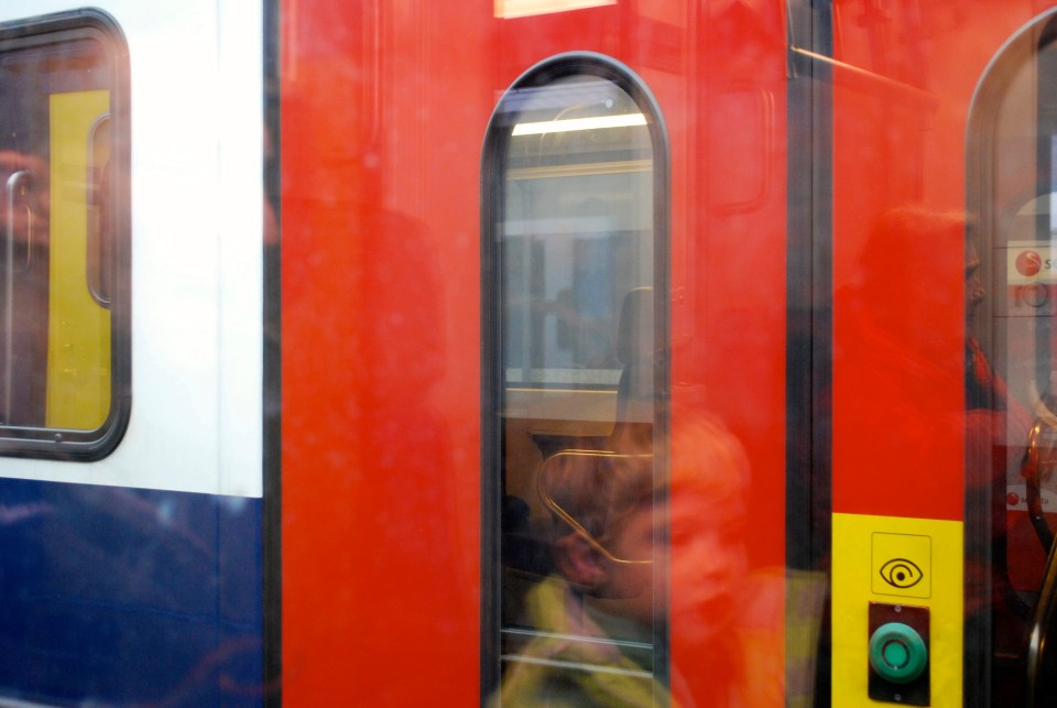 reflection of passengers in closed door of train